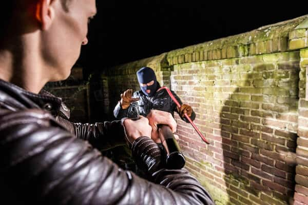 A Police Aiming Pistol Towards Scared Cracksman At Night